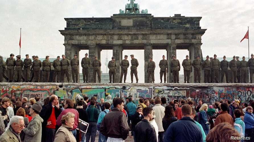 "FILE PHOTO 11NOV89 - East Berlin border guards stand atop the Berlin Wall in front of the Brandeburg Gate in this November 11, 1989 file photo. The 10th anniversary off the ""fall"" of the Berlin wall is coming up on November 10, 1999. - RTXJABH"