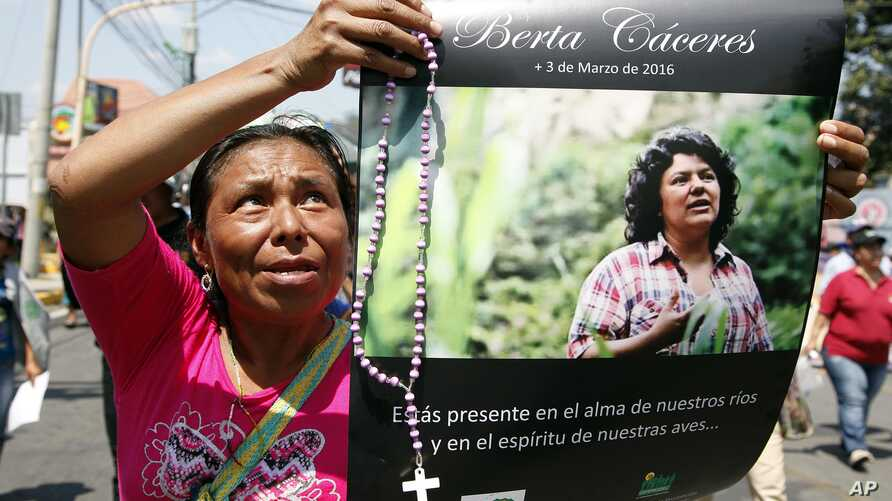 A woman holds up a poster with a photo of slain environmental leader Berta Caceres, during a protest march in Tegucigalpa, Honduras, March 16, 2016. Authorities said that unidentified gunmen killed Nelson Garcia, a colleague of Caceres, who was slain