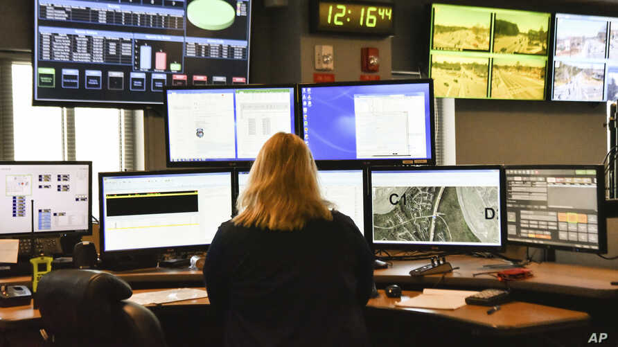 FILE- A dispatcher works at a desk station with a variety of screens used by those who take 911 emergency calls in Roswell, Ga., March 15, 2018. The Roswell call center is one of the few in the United States that accepts text messages.