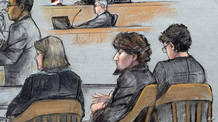 In this courtroom sketch, Assistant U.S. Attorney Aloke Chakravarty, left, is depicted addressing the jury as defendant Dzhokhar Tsarnaev, second from right, sits between his defense attorneys during closing arguments in Tsarnaev's federal death pena