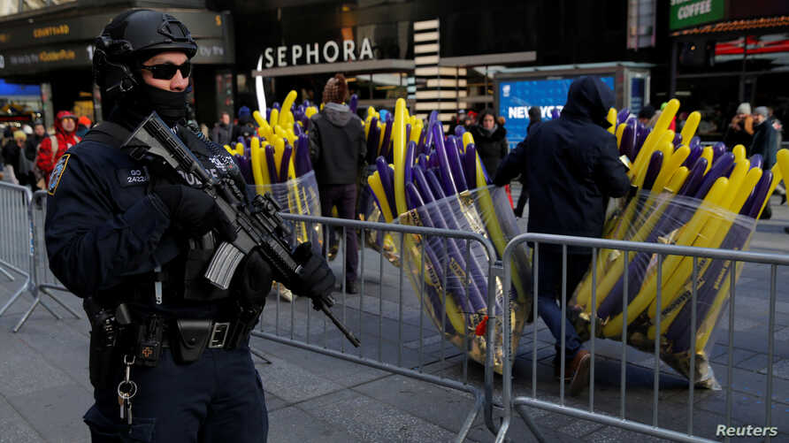 A member of the New York Police Department's Counterterrorism Bureau monitors security in Times Square ahead of New Year's celebrations in Manhattan, Dec. 29, 2017.