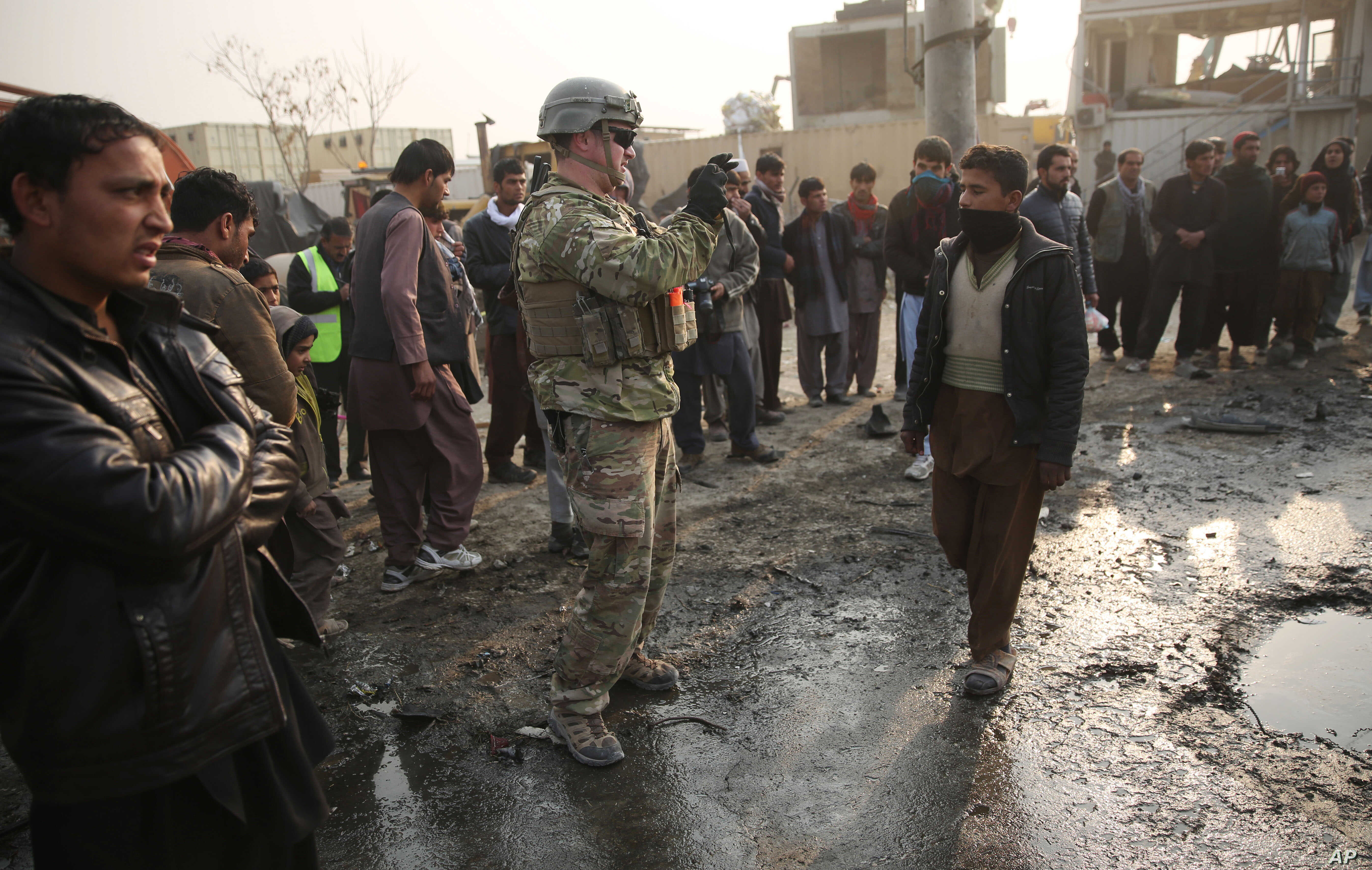 A U.S. soldier, center, takes a photo at the site of a suicide car bomb attack near the headquarters of the European police training mission in Kabul, Afghanistan, Jan. 5, 2015.
