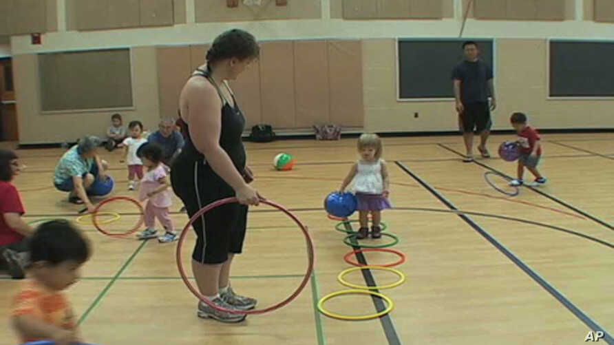 Catherine Byrne and her daughter Bridget, 3, attend a mobile gym class at an elementary school gymnasium in the Washington suburbs.