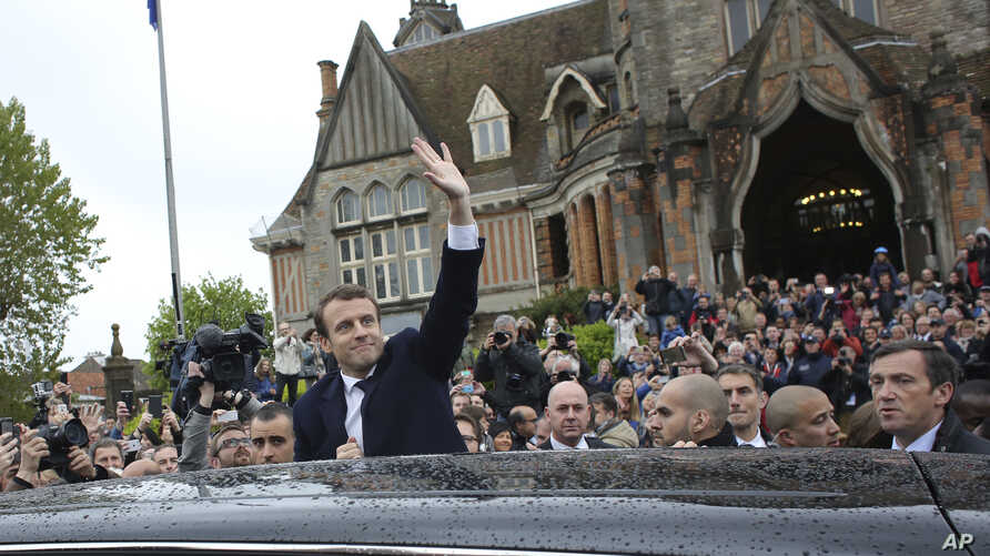 French independent centrist presidential candidate Emmanuel Macron, center, waves as he leaves the polling station after casting his ballot in the presidential runoff election in Le Touquet, France, May 7, 2017.