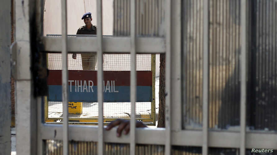 A policeman walks inside the Tihar Jail in New Delhi March 11, 2013. The driver of the bus in which a young Indian woman was gang-raped and fatally injured in December hanged himself in his jail cell on Monday, prison authorities said, but his family