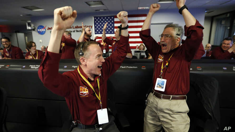 Engineers Kris Bruvold, left, and Sandy Krasner celebrate as the InSight lander touches down on Mars in the mission support area of the space flight operation facility at NASA's Jet Propulsion Laboratory in Pasadena, Calif., Nov. 26, 2018.