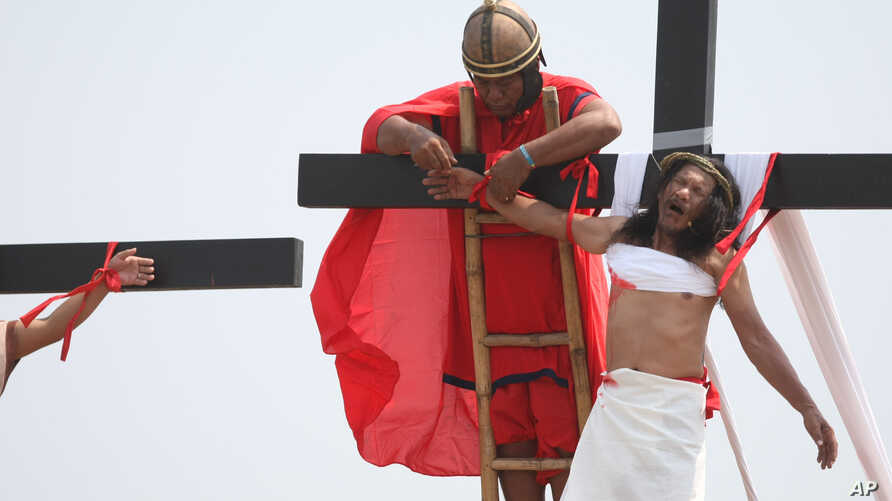 A volunteer dressed as a Roman centurion helps lower Ruben Enaje after he was nailed to a wooden cross during a Good Friday reenactment in Cutud, Pampagna province, northern Philippines, March 25, 2016.