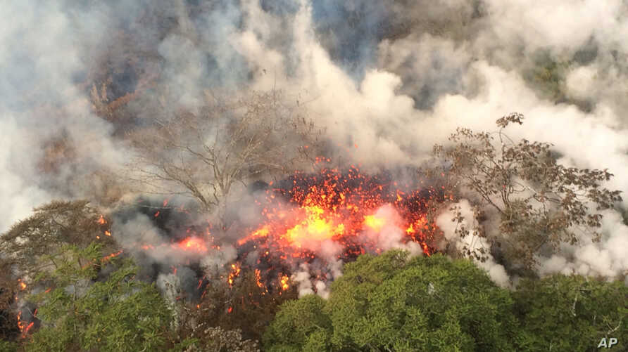 This May 16, 2018, image provided by the U.S. Geological Survey shows lava spattering from an area between active Fissures 16 and 20 photographed on the lower east rift of the Kilauea volcano, near Pahoa, Hawaii.
