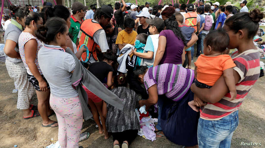 Central American migrants receive donated clothes as they take a break from traveling in their caravan, on their journey to the U.S., in Matias Romero, Oaxaca, Mexico, April 3, 2018.