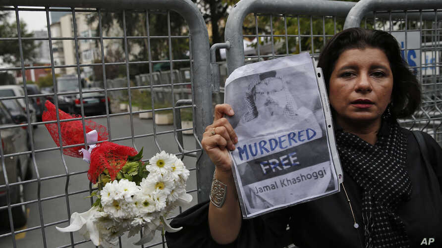 Sahar Zeki, an activist and a friend of slain Saudi writer Jamal Khashoggi, holds a picture of him, after attaching a bouquet of flowers, at the barriers blocking the road leading to the Saudi Arabia's consulate in Istanbul, Tuesday, Oct. 23, 2018. S