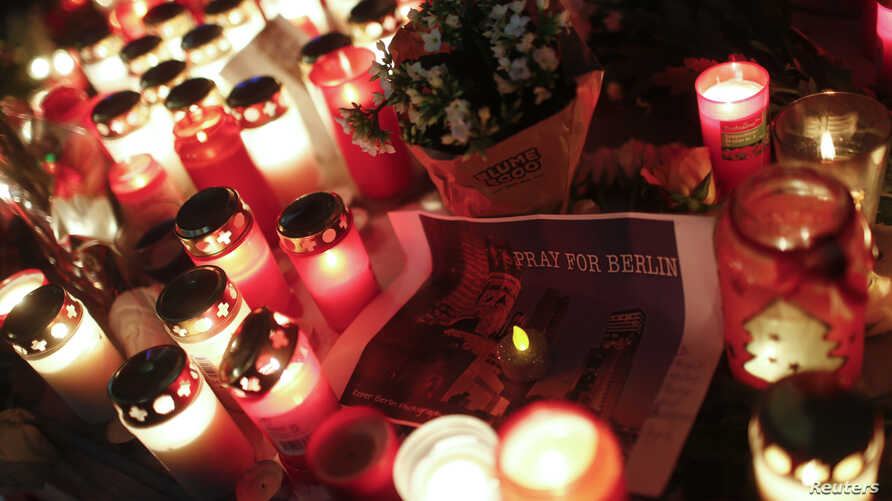 Candles burn at a Christmas market at Breitscheidplatz in Berlin, Germany on Dec. 20, 2016, to commemorate the 12 victims of a truck that ploughed into the crowded market.