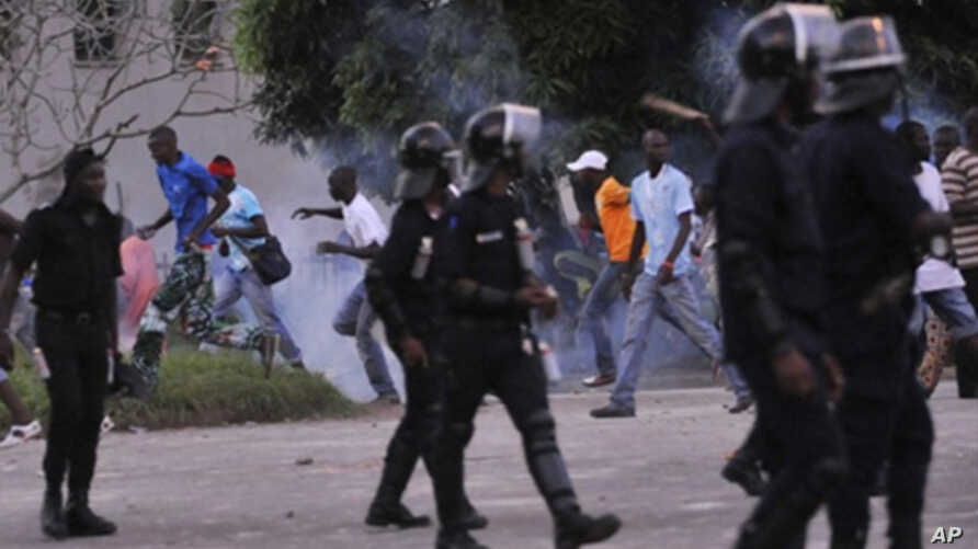 Demonstraters disperse because of tear gas thrown into the crowd by riot police during clashes in Abidjan on November 19, 2010.