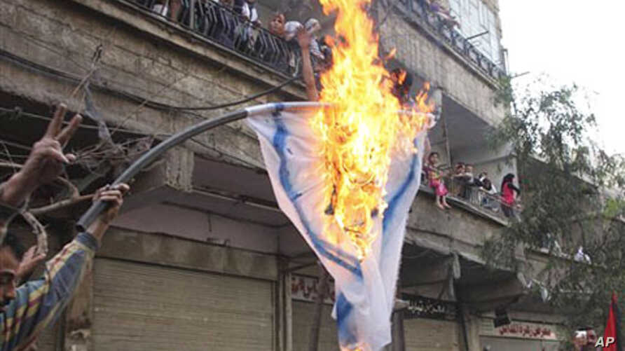 Palestinian mourners burn an Israeli flag during a funeral procession of three Palestinians who killed when Israeli soldiers opened fire on Sunday at protesters at Syria's border with the Israeli-controlled Golan Heights, May 16 2011
