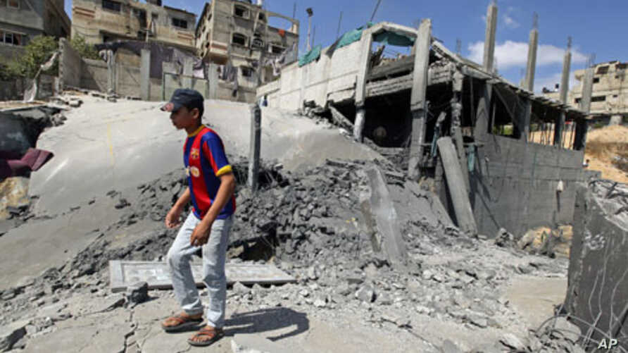 A Palestinian walks on rubble after an Israeli air strike damaged a sports facility belonging to the Islamic Jihad group in Beit Lahiya in the northern Gaza Strip, August 25, 2011