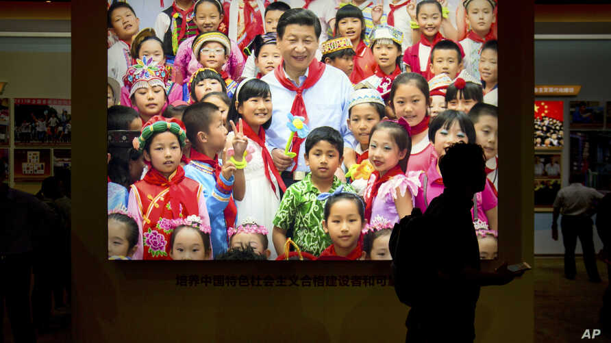 FILE - A visitor walks past a photo, Sept. 28, 2017, of Chinese President Xi Jinping surrounded by children at an exhibition highlighting five years of progress under Xi's leadership in Beijing. The birthrate in China fell in 2017 despite the easing