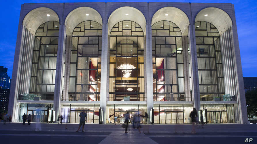 FILE - Pedestrians walk in front of the Metropolitan Opera house at New York's Lincoln Center, Aug. 1, 2014. New York's Metropolitan Opera stopped a performance Saturday after someone sprinkled an unknown powder into the orchestra pit.