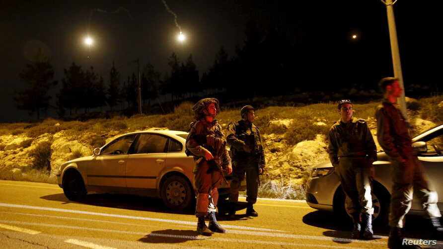 Israeli soldiers stand guard near the Jewish settlement of Otniel in the West Bank, Jan. 17, 2016, after a female resident of the settlement was stabbed to death in her home.