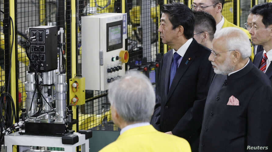 Indian Prime Minister Narendra Modi and Japan's Prime Minister Shinzo Abe inspect Fanuc Corp's factory in Oshino village, Yamanashi Prefecture, Japan in this photo taken by Kyodo, Oct. 28, 2018.