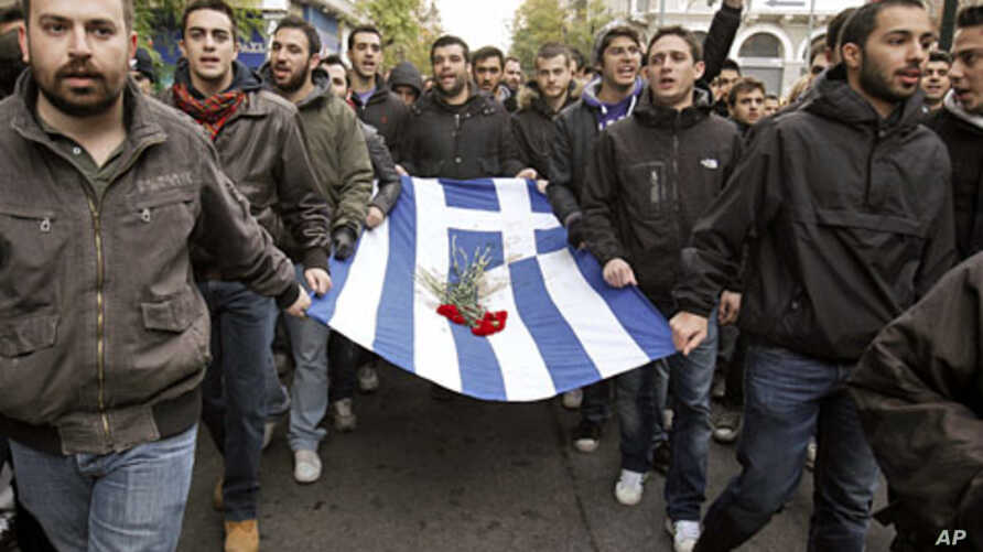 Students carry a blood-stained Greek flag during a rally in Athens marking the anniversary of a 1973 students uprising against the dictatorship then ruling Greece November 17, 2011