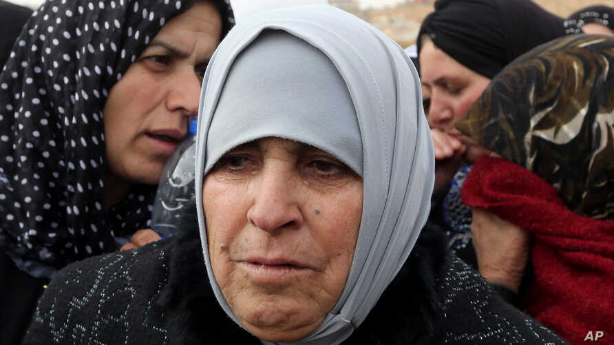 FILE - Umm Mohammed, 68, cries during an interview with The Associated Press as hundreds of Syrian women stand in line waiting to collect aid from relief agencies helping Syrian refugees.