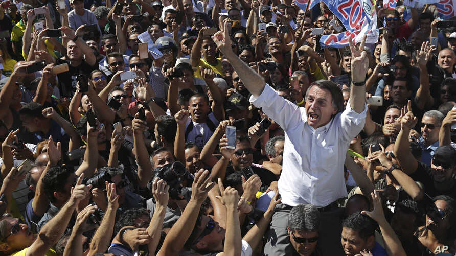 National Social Liberal Party presidential candidate Jair Bolsonaro greets supporters as he gets a shoulder ride from a member of his security detail, in Brasilia's Ceilandia neighborhood, Sept. 5, 2018.