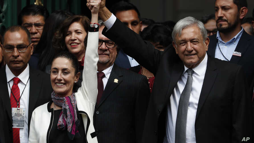 The first elected female mayor of Mexico City Claudia Sheinbaum and President Andres Manuel Lopez Obrador lift their arms in unison after she was sworn into office, in Mexico City, Dec. 5, 2018.