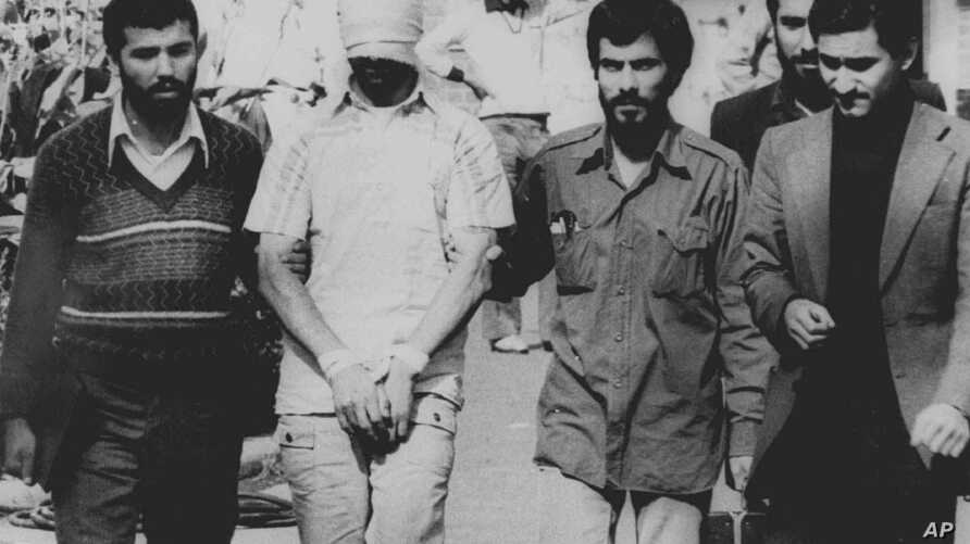 FILE - One of the U.S. hostages, blindfolded and with his hands bound, is being displayed to the crowd outside the U.S. Embassy in Tehran by Iranian hostage takers, Nov. 9, 1979.