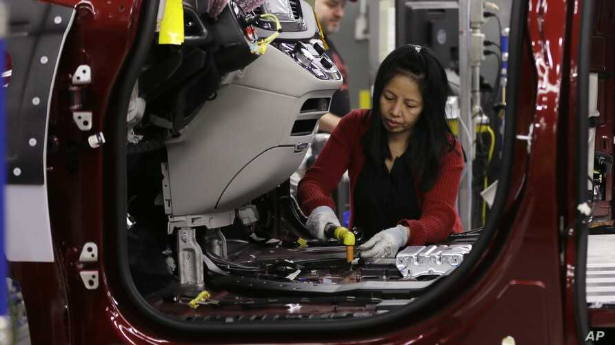 FILE - An employee works on a 2017 Chrysler Pacifica on the assembly line at the Windsor Assembly Plant, in Windsor, Canada, May 6, 2016.