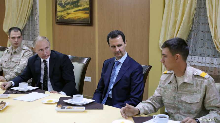 Russian President Vladimir Putin (2nd L) and Syrian President Bashar al-Assad (2nd R) meet with servicemen as they visit the Hmeymim air base in Latakia Province, Syria, Dec. 11, 2017.