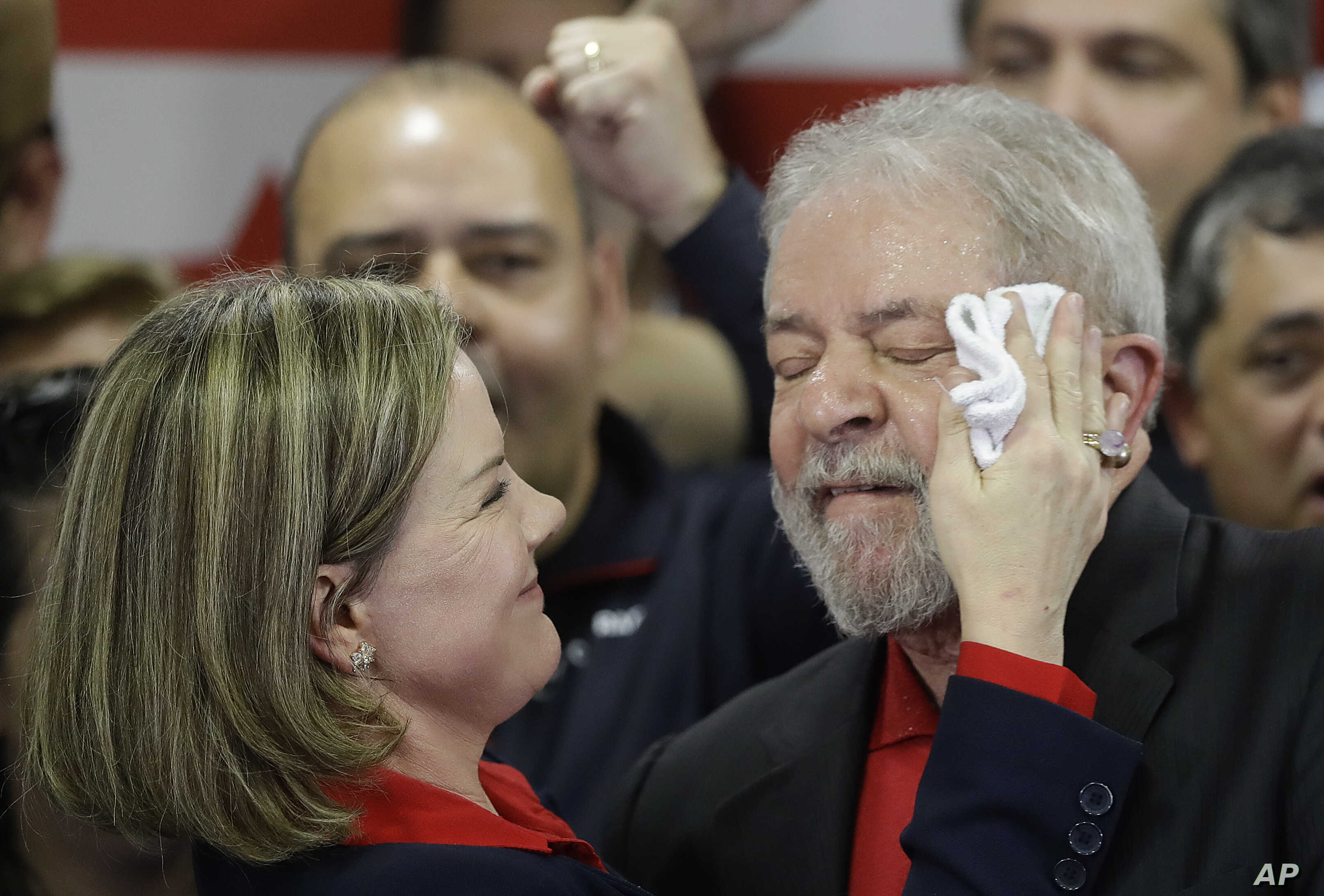 Worker's Party president, Sen. Gleisi Hoffmann, wipes sweat from the face of former Brazilian President Luiz Inacio Lula da Silva at the end of a brief speech he delivered to media and supporters at the party's headquarters in Sao Paulo, Brazil, Thur