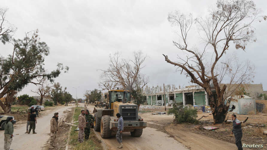 FILE - Members of East Libyan forces open Tripoli road after they captured the final holdout of Islamist-led rivals in the southwest of Benghazi, Libya, March 21, 2017. On Saturday, they took control of the central Souq al-Hout neighborhood of Bengha