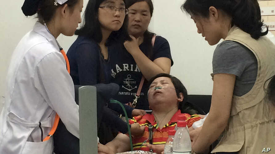 A relative of Shanghai passengers on board a cruise ship that capsized in central China, is attended to by a medical worker as she waits for answers at a government office in Shanghai, China, Tuesday, June 2, 2015. Relatives storm a government office...