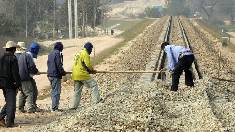 FILE - Construction workers rake gravel on railroad tracks in Thanalaeng, Laos, Feb. 13, 2008.