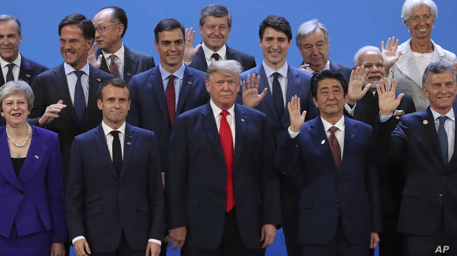 President Donald Trump, front center, stands with other world leaders as they pose for a group picture at the start of the G-20 Leader's Summit inside the Costa Salguero Center in Buenos Aires, Argentina, Nov. 30, 2018. From left, front, are Britain'