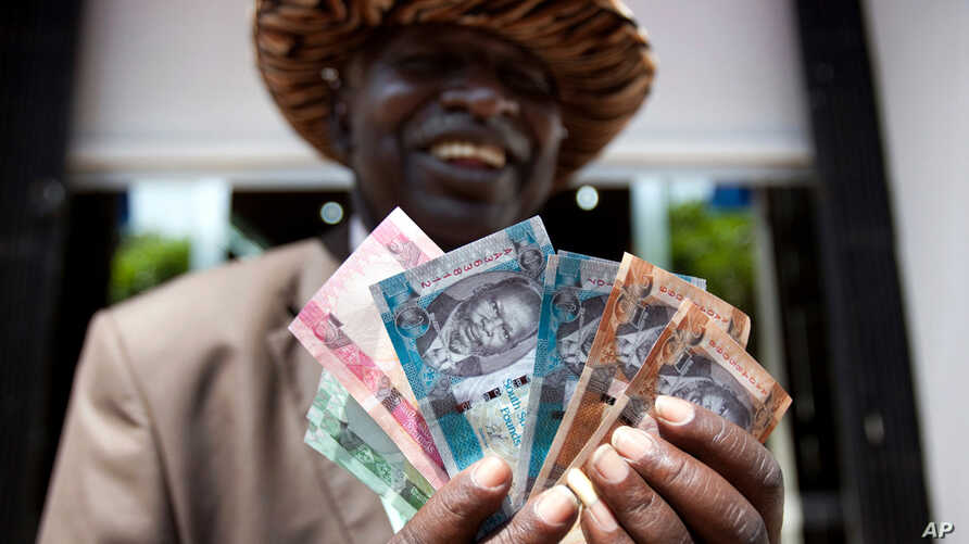 July 19: A man from South Sudan displays new currency notes outside the Central Bank of South Sudan in Juba. South Sudan started rolling out its new currency on Monday: the South Sudan Pound.  REUTERS/Benedicte Desrus