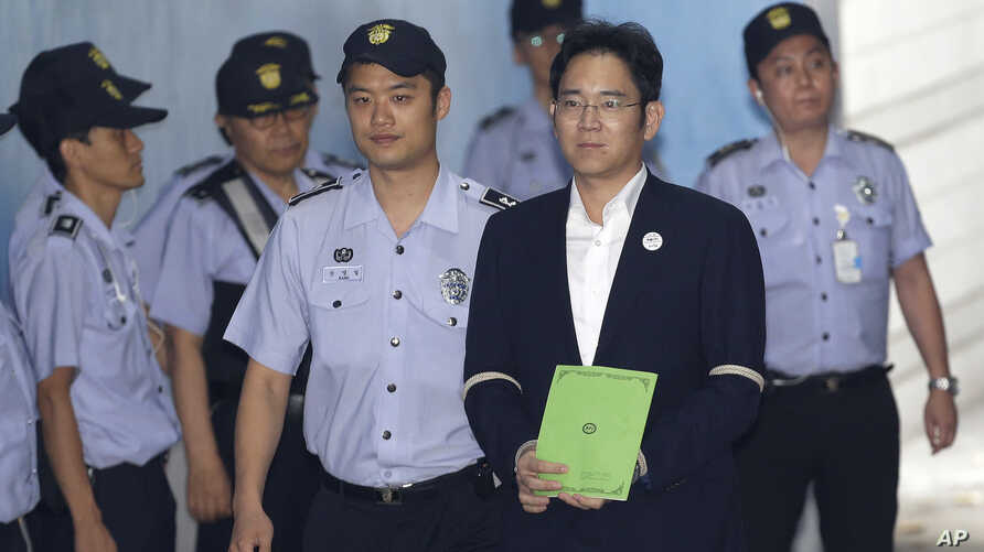 Lee Jae-yong, second from right, vice chairman of Samsung Electronics Co., arrives for his trial at the Seoul Central District Court in Seoul, South Korea, Aug. 7, 2017.