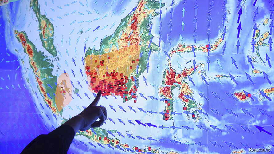 An officer points to fires or hot spots in Kalimantan, Indonesian part of Borneo, on a screen at the Fire Command Post at the Ministry of Environment and Forestry in Jakarta Sept. 22, 2015 in this photo taken by Antara Foto.