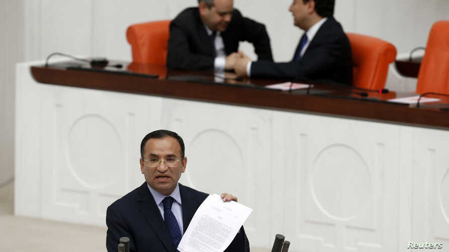Justice Minister Bekir Bozdag addresses the Turkish Parliament during a debate in Ankara March 19, 2014. Parliament convened in the capital Ankara for the hearing of a prosecutor report allegedly outlining the role of four former ministers in a corru