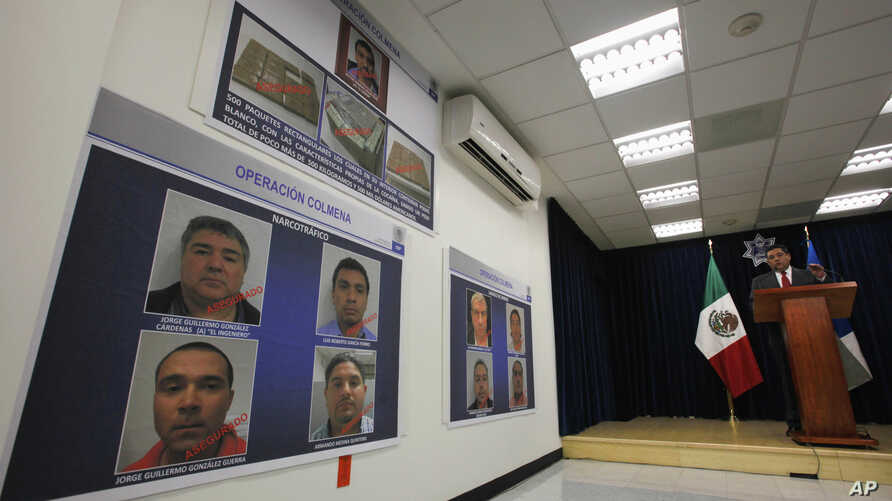 Ramon Pequeno, head of Mexico's federal police anti-narcotics division, speaks at a press conference next to photos of nine arrested suspects in Mexico City, Wednesday March 23, 2011.
