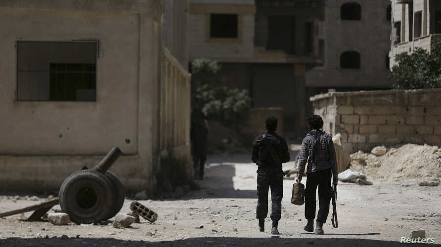 FILE - Fighters from the Free Syrian Army's Al Rahman legion walk towards their positions in Jobar, a suburb of Damascus, Syria.