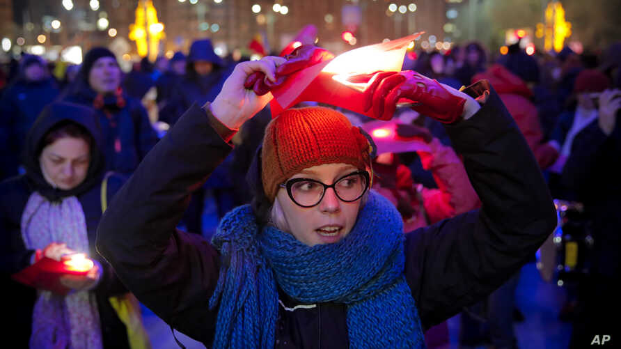 A woman holds a red paper as people display Romania's red, yellow and blue flag during an anti-government protest in Bucharest, Romania, Dec. 1, 2018, as Romanians celebrate 100 years since the country became a modern-day state.