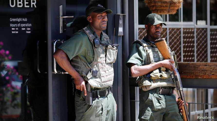 Private security guard stand outside Uber offices in Parktown, a suburb of Johannesburg, South Africa, March 10, 2017.