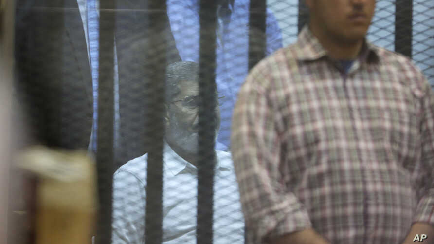 An Egyptian plain clothed policemen guards Egypt's ousted Islamist President Mohammed Morsi as he sits in a soundproof glass cage inside a makeshift courtroom at Egypt's national police academy in Cairo, Egypt, Tuesday, April 21, 2015. An Egyptian cr