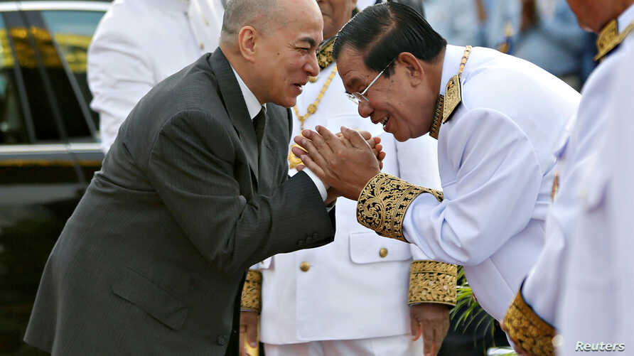 Cambodia's King Norodom Sihamoni is greeted by prime minister Hun Sen during the celebration marking the 64th anniversary of the country's independence from France, in Phnom Penh, Cambodia, Nov. 9, 2017.