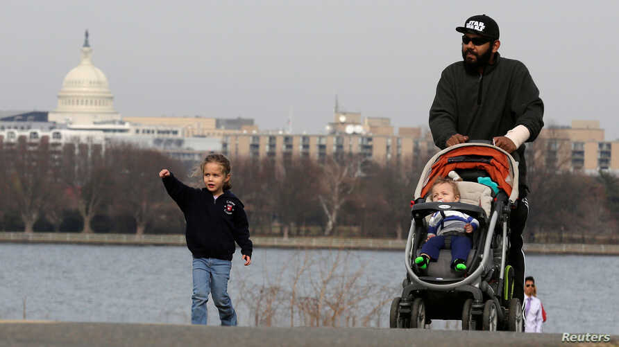 FILE  - A man walks with his children during unseasonably warm weather in Washington, Feb. 22, 2017.