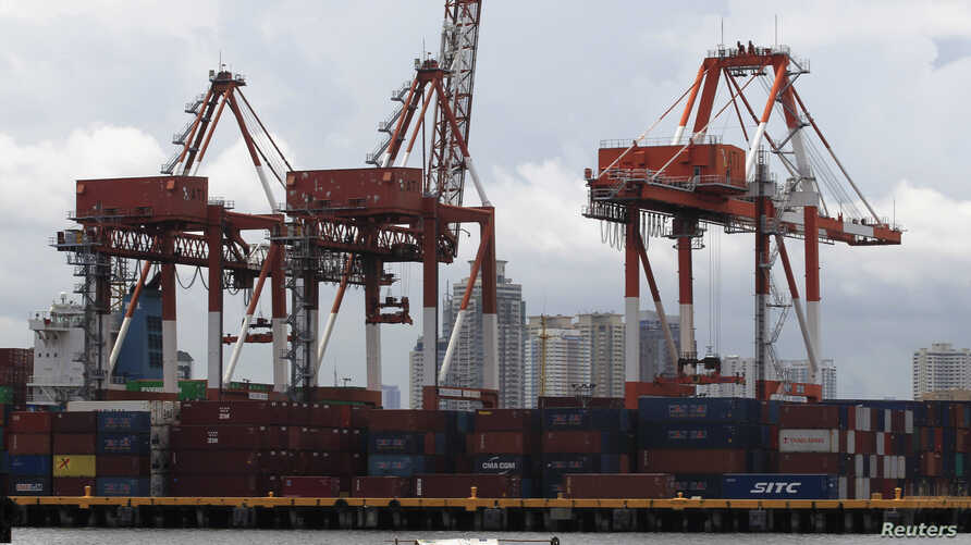 FILE - A small boat moves past one of the country's busiest ports at a portion of Manila Bay.