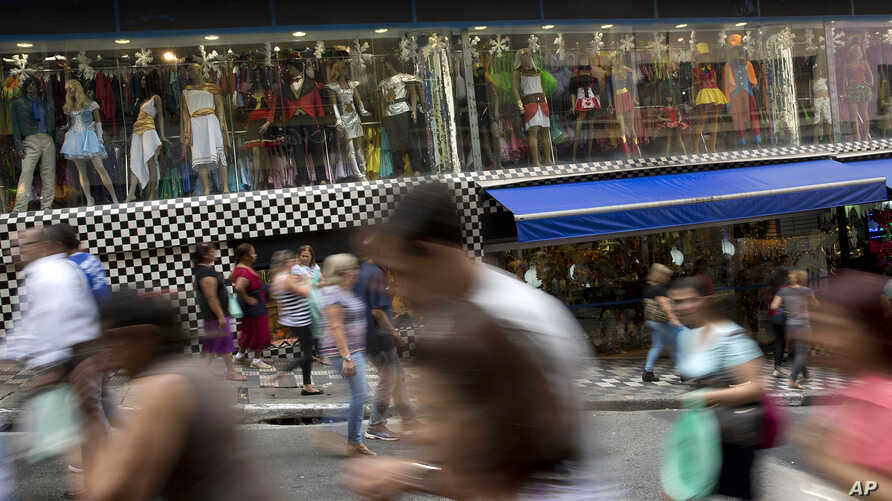 FILE - A photo taken with a slow shutter speed shows people walk through a shopping district in Sao Paulo, Brazil, Dec. 1, 2015.