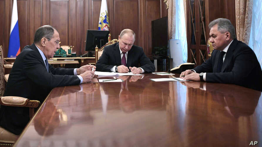 Russian President Vladimir Putin, center, attends a meeting with Russian Foreign Minister Sergey Lavrov, left, and Defense Minister Sergei Shoigu in the Kremlin in Moscow, Feb. 2, 2019. Putin said Russia would abandon the 1987 Intermediate-range Nucl