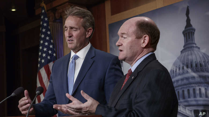 Sen. Jeff Flake, R-Ariz. (L) and Sen. Chris Coons, D-Del., talk to reporters after making speeches on the Senate floor calling for a resolution to back the U.S. intelligence community findings that Russia interfered in the 2016 election and calling f