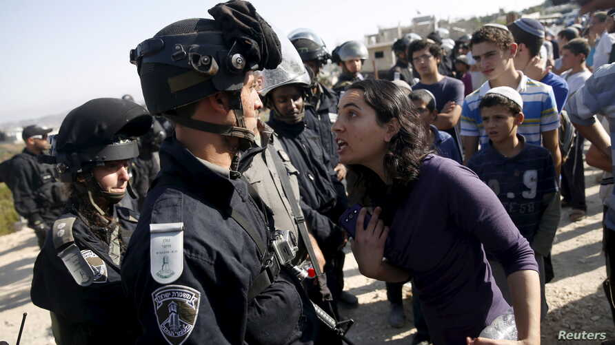 A young Jewish settler (R) speaks with an Israeli police officer near buildings slated for demolition by order of Israel's high court, in the West Bank Jewish settlement of Beit El near Ramallah, July 28, 2015.